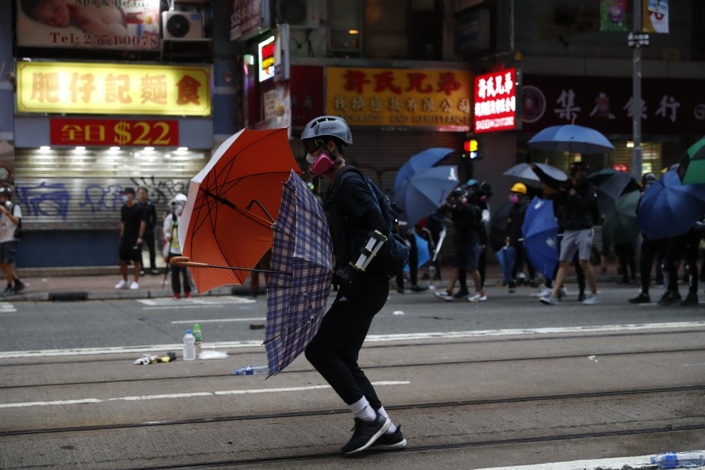 """In this Oct. 6, 2019, photo, protestors clash with police in Hong Kong. Shouting """"Wearing mask is not a crime,"""" tens of thousands of protesters braved"""