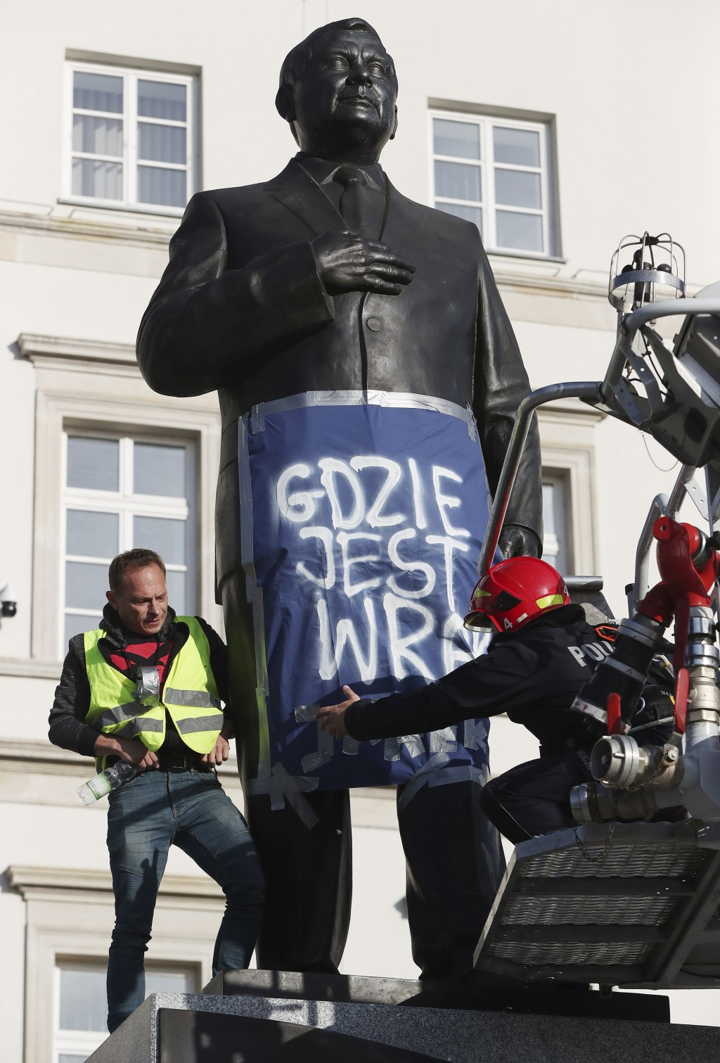 A man stands on a monument to Poland's late president Lech Kaczynski in downtown Warsaw, Poland, Friday, Oct. 11, 2019. He wrapped it in a banner read