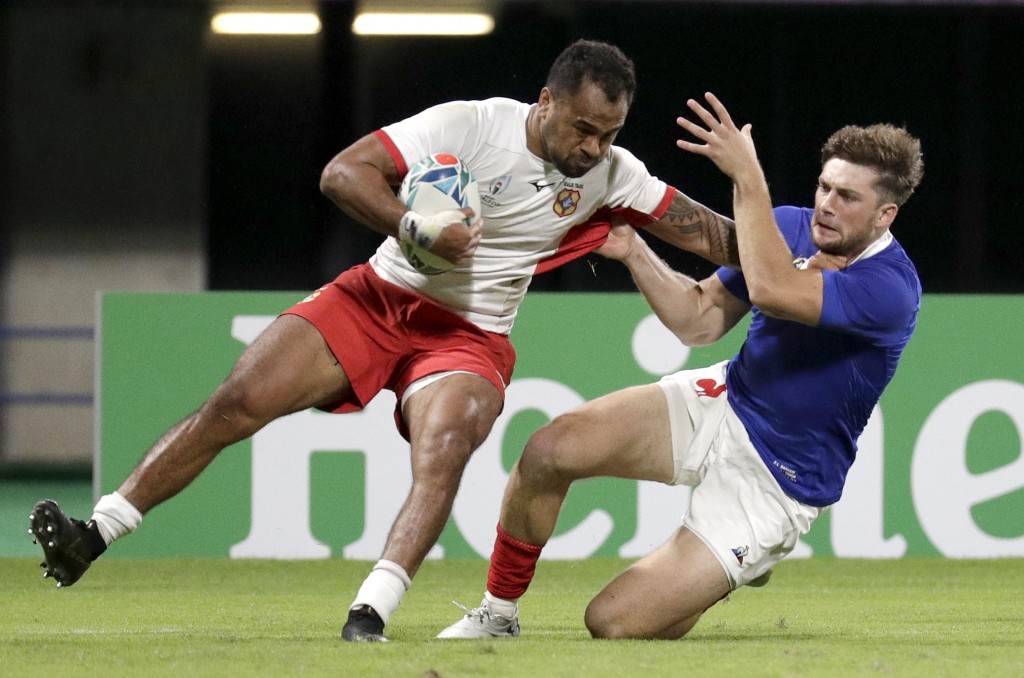Tonga's Atieli Pakalani, left, is tackled by a French defender during the Rugby World Cup Pool C game at Kumamoto Stadium between France and Tonga in ...