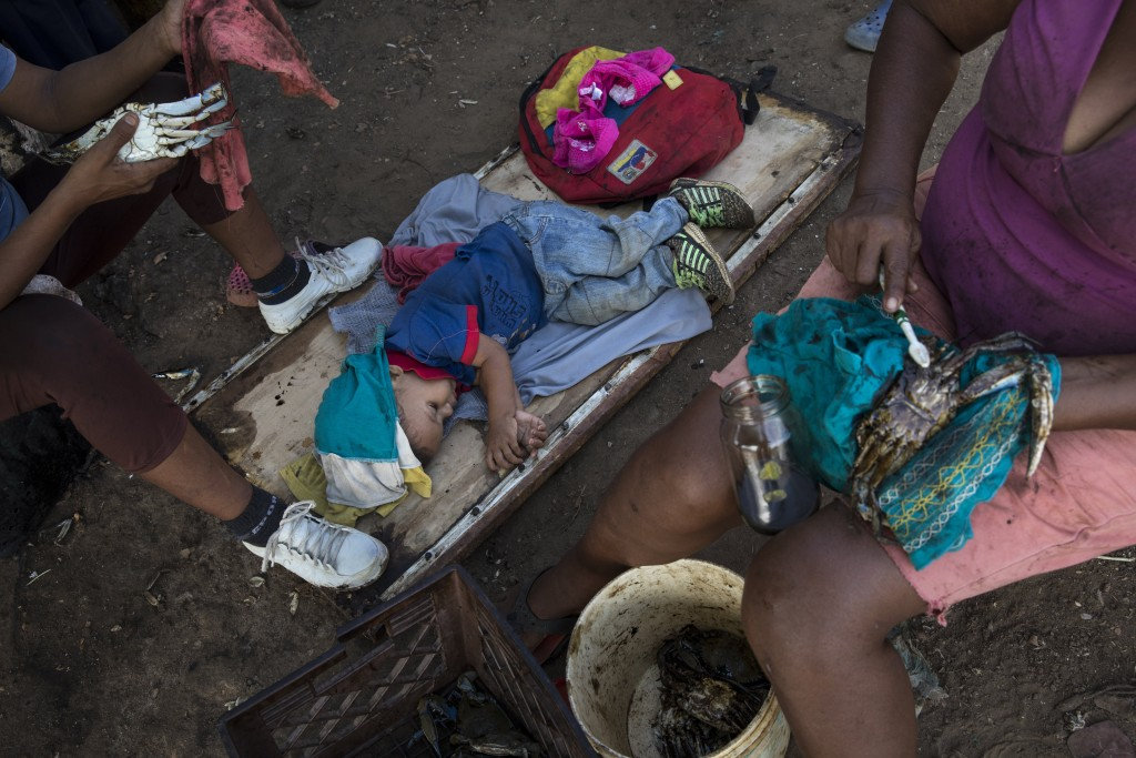 A boy sleeps as locals clean oil off of freshly harvested crabs from Lake Maracaibo, on Punta Gorda beach in Cabimas, Venezuela, May 21, 2019. Fisherm...