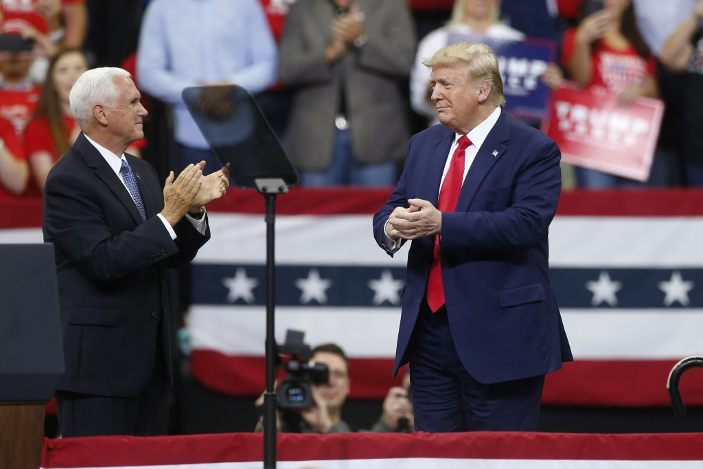 Vice President Mike Pence applauds President Donald Trump after Pence introduced him during a campaign rally Thursday, Oct. 10, 2019, in Minneapolis. ...