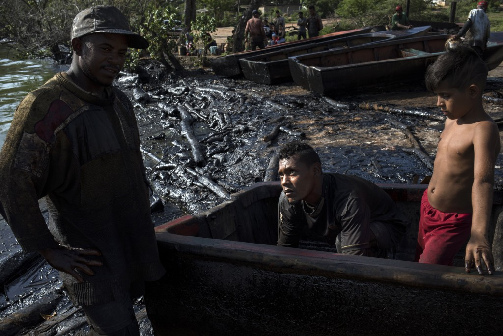 Fishermen Erick Alejandro, left, and Kelvin Alcala remove oil accumulated inside their boat after a workday on the oil-soaked shore of Lake Maracaibo ...