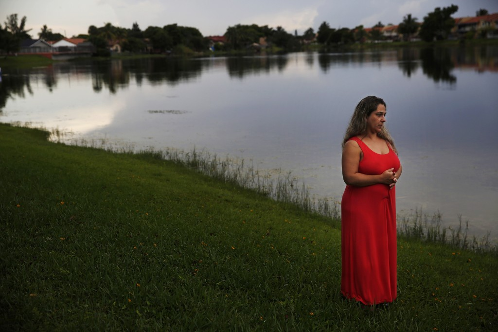 In this Aug. 6, 2019, photo, Barbara Rodriguez poses for a photo outside of her home in Hialeah, Fla. Her husband, Pablo Sanchez, is seeking asylum in...