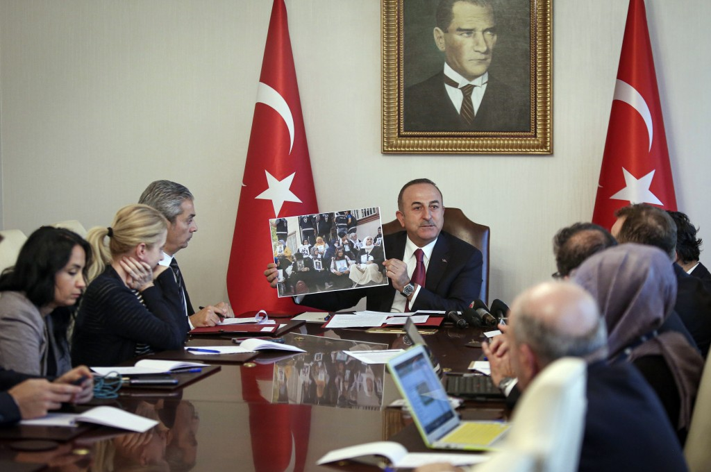 Turkish Foreign Minister Mevlut Cavusoglu shows a photograph of a group of mothers who say their children have been abducted by outlawed Kurdish rebel