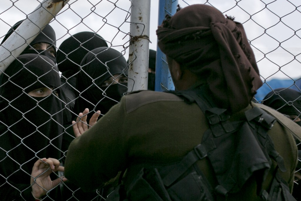 In this March 31, 2019, photo, women speak to guards at the gate that closes off the section for foreign families who lived in the Islamic State's so-