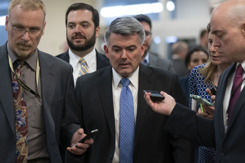 FILE - In this March 13, 2019 file photo, reporters pose questions to Sen. Cory Gardner, R-Colo., on his way to a vote at the Capitol in Washington. (...