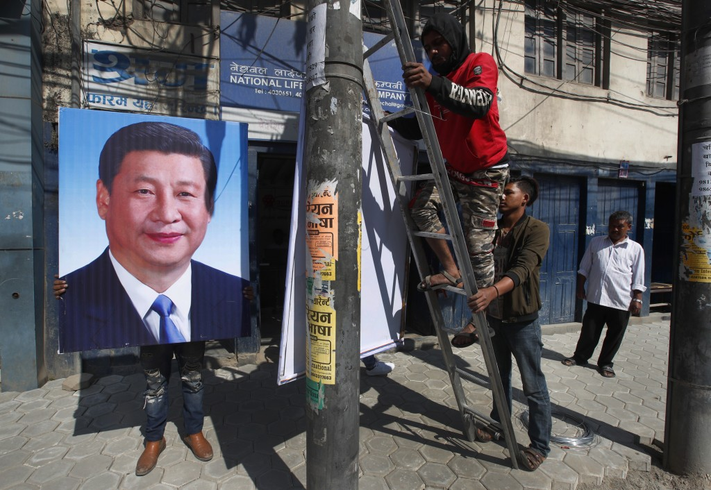 Nepalese workers work to hang portraits of Chinese president Xi Jinping in Kathmandu, Nepal, Friday, Oct. 11, 2019. Officials from both China and Nepa