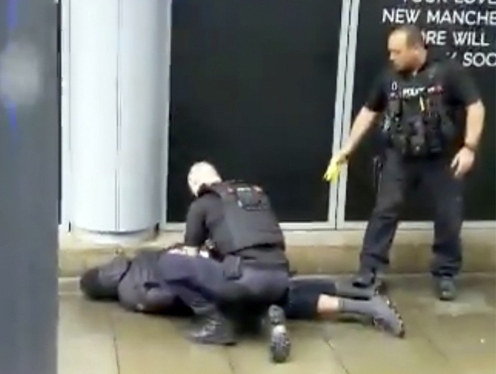 In this image taken from mobile phone footage, police arrest a man outside the Arndale Centre in Manchester, England, Friday October 11, 2019, after a