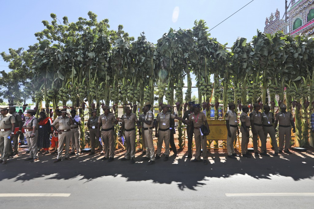 Police personnel stand in the shade of banana trees at the entrance at the entrance to Mamallapuram, where Indian Prime Minister Narendra Modi and Chi...