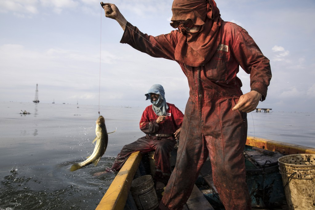 """Fishermen wearing oil stained uniforms from Venezuela's state-run oil firm PDVSA, catch bass known as """"robalo"""" near La Salina crude oil shipping termi..."""