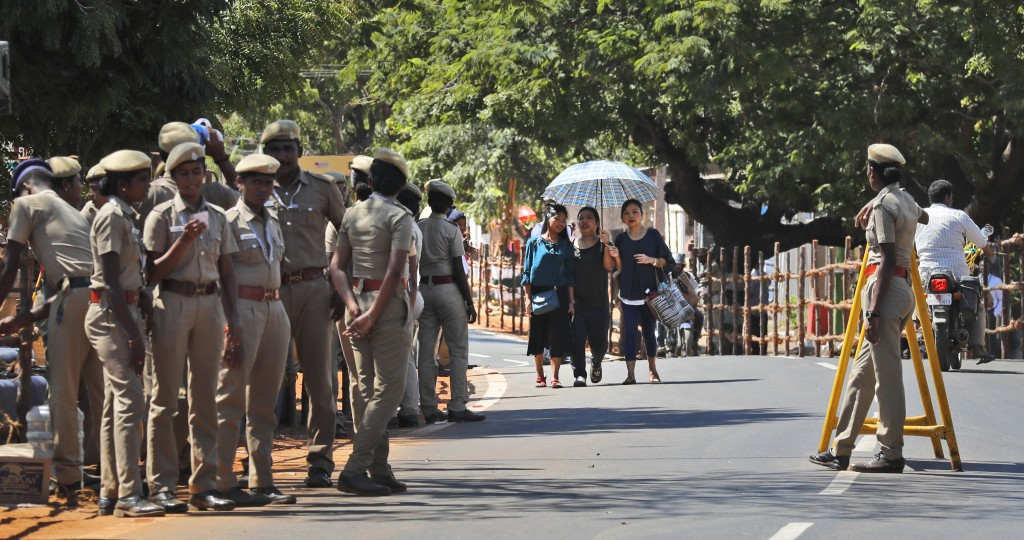 A group of tourists walk past police personnel keeping guard at Mamallapuram, where Indian Prime Minister Narendra Modi and Chinese President Xi Jinpi...