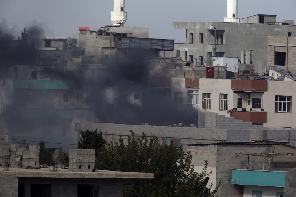 Smoke from a fire caused by an incoming mortar fired from the Syrian side, billows in Akcakale, Sanliurfa province, southeastern Turkey, Thursday, Oct...