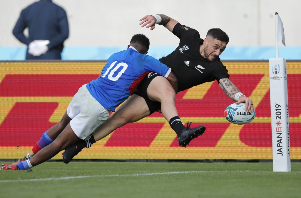 In this Oct. 6, 2019, photo, New Zealand's T J Perenara looks to score a try as he is tackled by Namibia's Helarius Kisting during the Rugby World Cup...