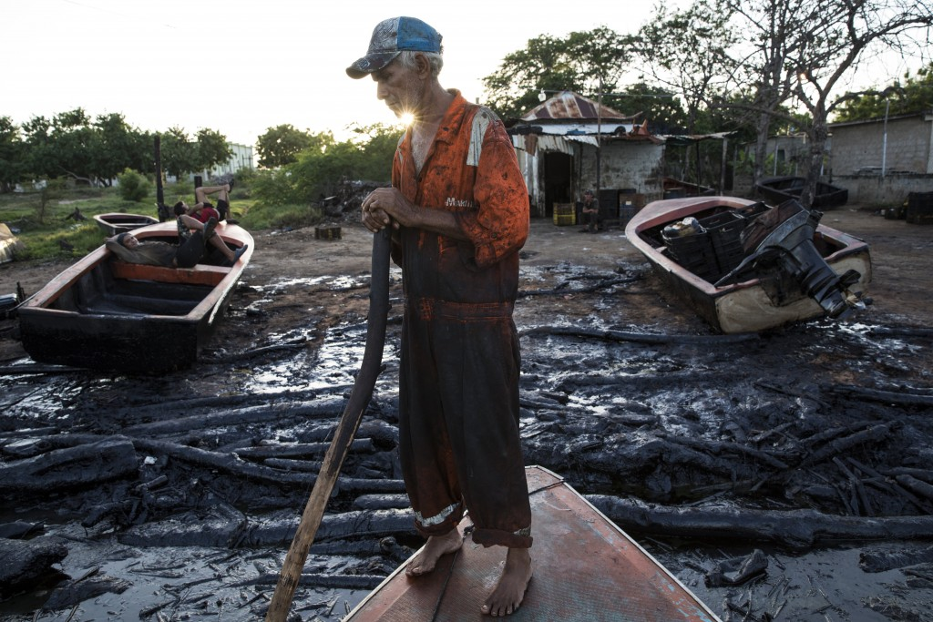 Fisherman William Vilchez stands on his boat on the oil-covered shoreline of Lake Maracaibo in Cabimas, Venezuela, May 18, 2019. The world's largest c...