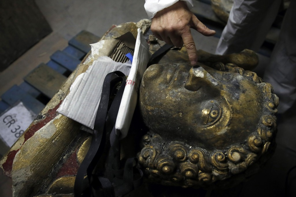 In this photo taken on Wednesday, Oct. 9, 2019, stone expert Jean-Didier Mertz, shows a broken nose of the golden angel that was once atop Notre Dame ...