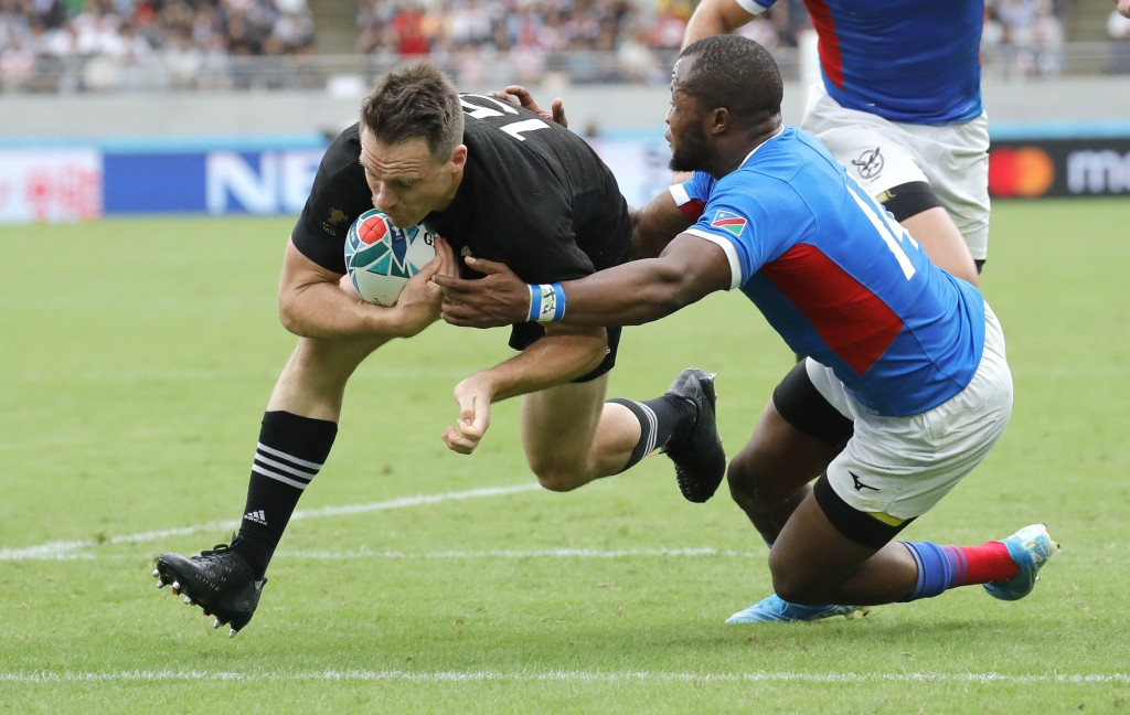 New Zealand's Ben Smith, left, dives across the line in the tackle of Namibia's Lesley Klim to score a try during the Rugby World Cup Pool B game at T