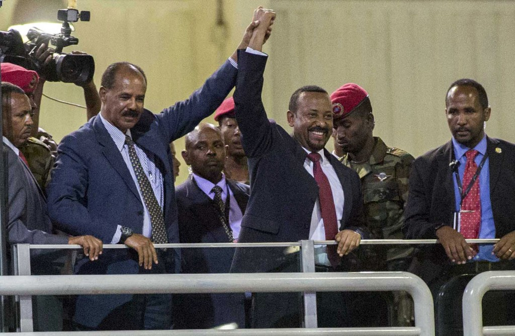 FILE - In this Sunday July 15, 2018 file photo, Eritrean President Isaias Afwerki, second left, and Ethiopia's Prime Minister Abiy Ahmed, center, hold...