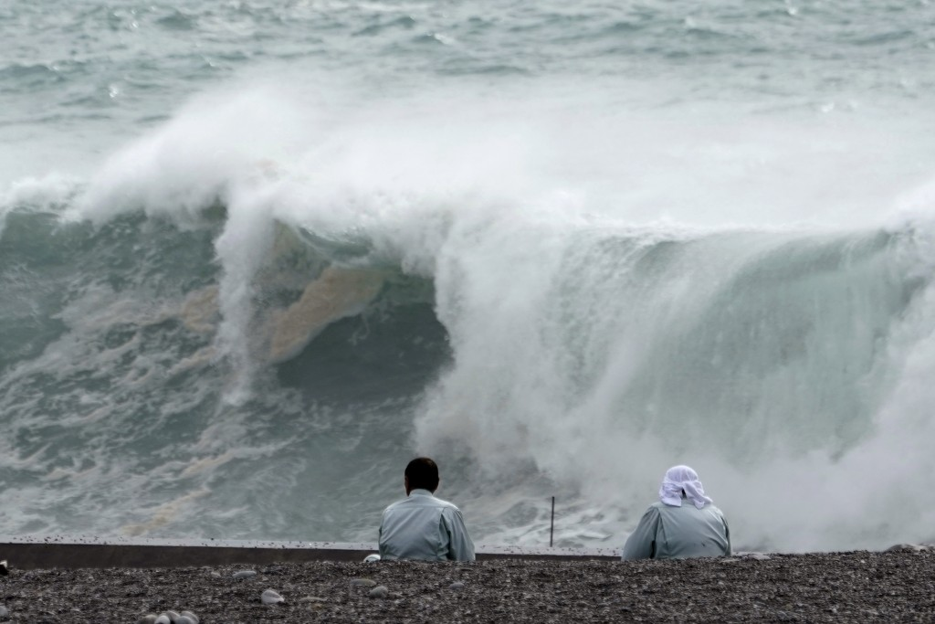 Men look at surging waves as Typhoon Hagibis approaches at a port in town of Kiho, Mie Prefecture, Japan Friday, Oct. 11, 2019. A powerful typhoon is ...