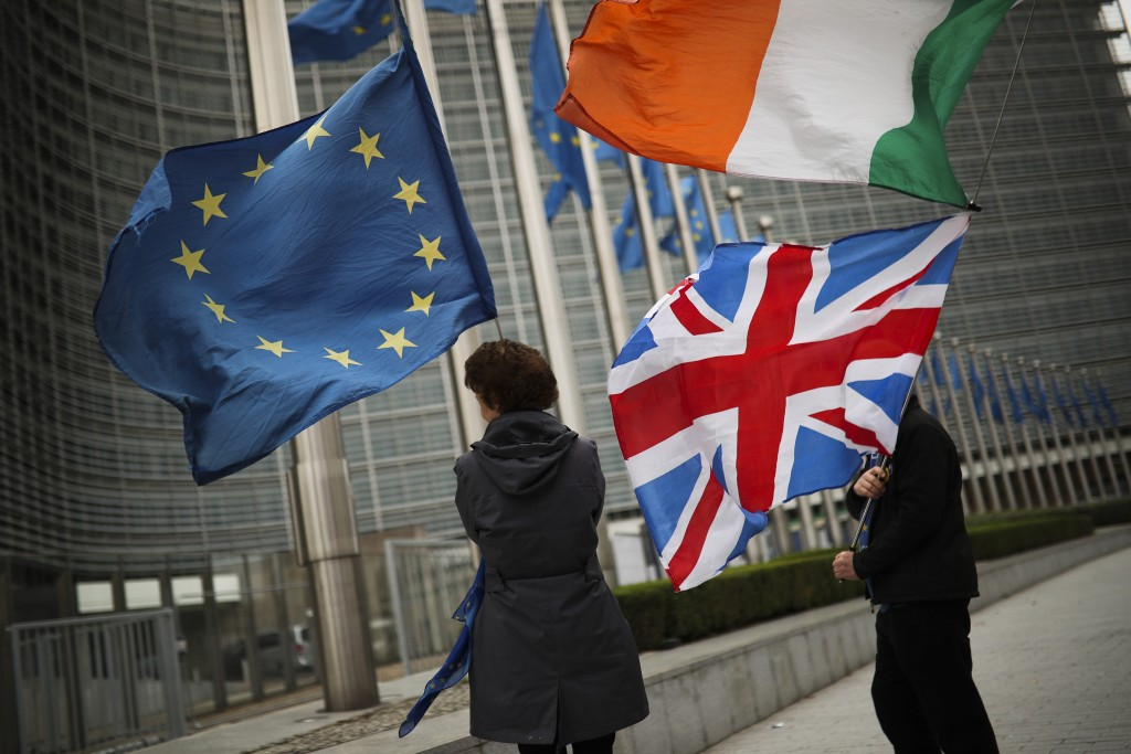 Two anti Brexit people hold EU, Ireland and Union Flags as they wait for the departure of UK Brexit secretary Stephen Barclay during his meeting with ...
