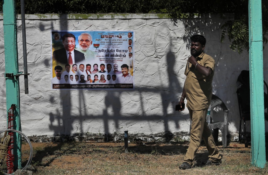 A man walks past a poster welcoming Indian Prime Minister Narendra Modi and Chinese President Xi Jinping, on the road leading to Mamallapuram, in sout