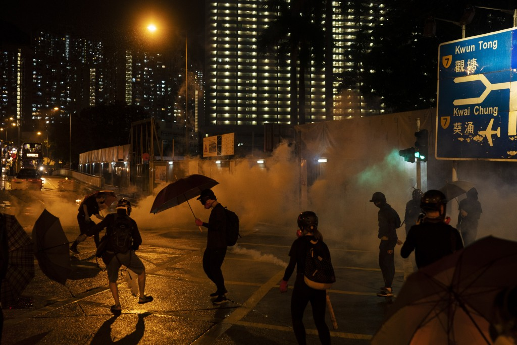 """In this Oct. 6, 2019, photo, protestors face police tear gas in Hong Kong. Shouting """"Wearing mask is not a crime,"""" tens of thousands of protesters bra"""