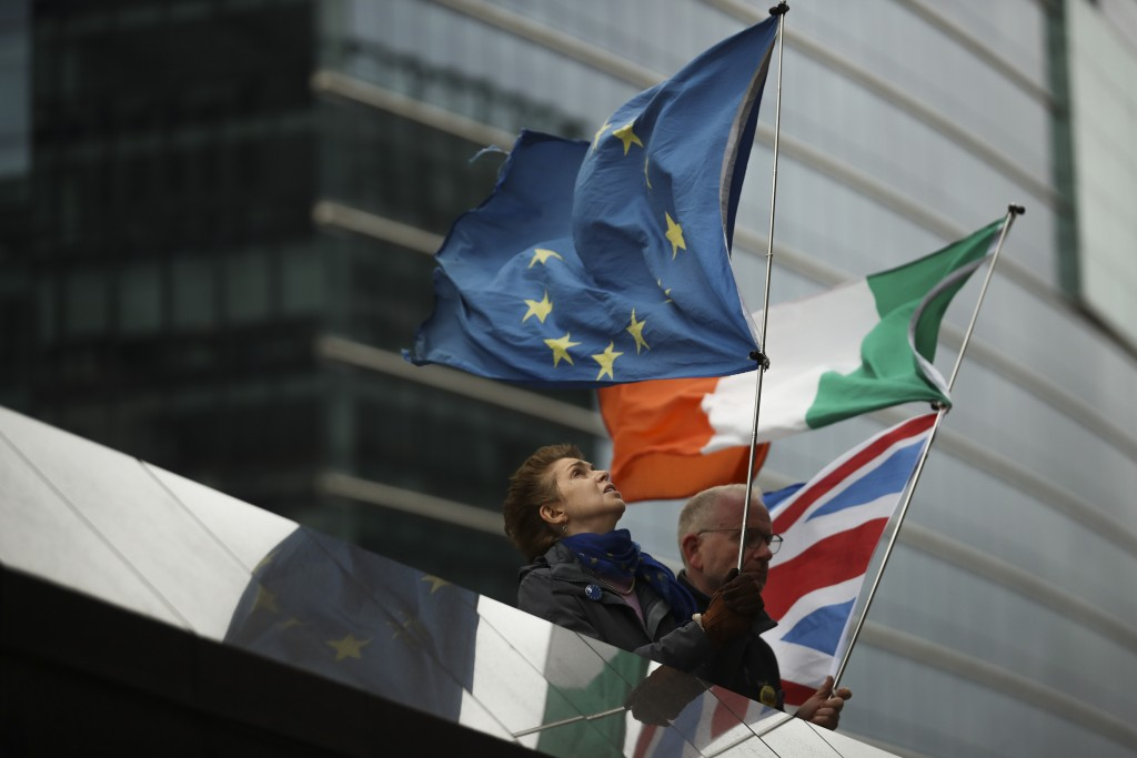 Two anti-Brexit people hold EU, Ireland and Union Flags stand outside the European Commission in Brussels, Friday, Oct. 11, 2019. EU negotiator Michel...