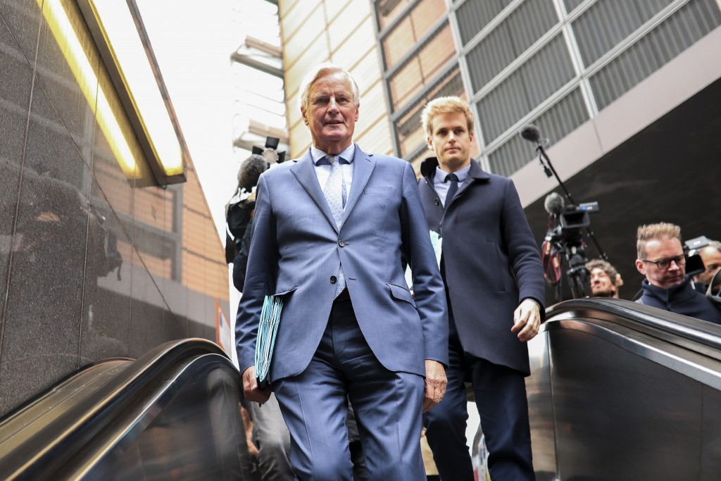 European Union chief Brexit negotiator Michel Barnier, left, rides an escalator on his way to a meeting at the Europa building in Brussels, Friday, Oc...