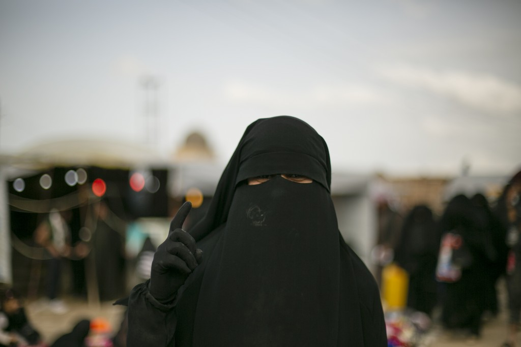 FILE - In this March 31, 2019, file, photo, a woman gestures for a portrait at al-Hol camp, which holds families of Islamic State members, in Hasakeh ...