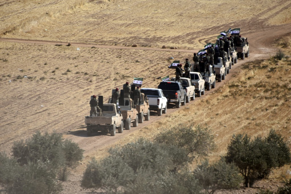 Turkey-backed FSA fighters are heading toward Syrian town of Tal Abyad from Turkish border town of Akcakale, Turkey, Thursday, Oct. 10, 2019. Turkish ...
