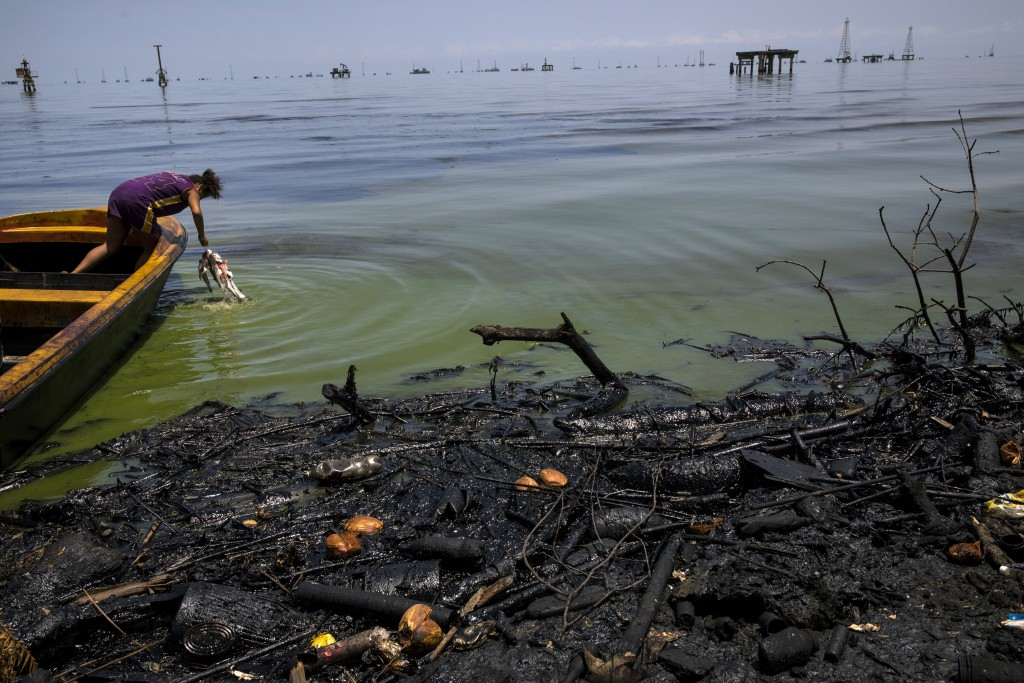Fabiola Elizalzabal washes fish caught by her father near La Salina crude oil shipping terminal on Lake Maracaibo, next to an oil-covered shore in Cab...