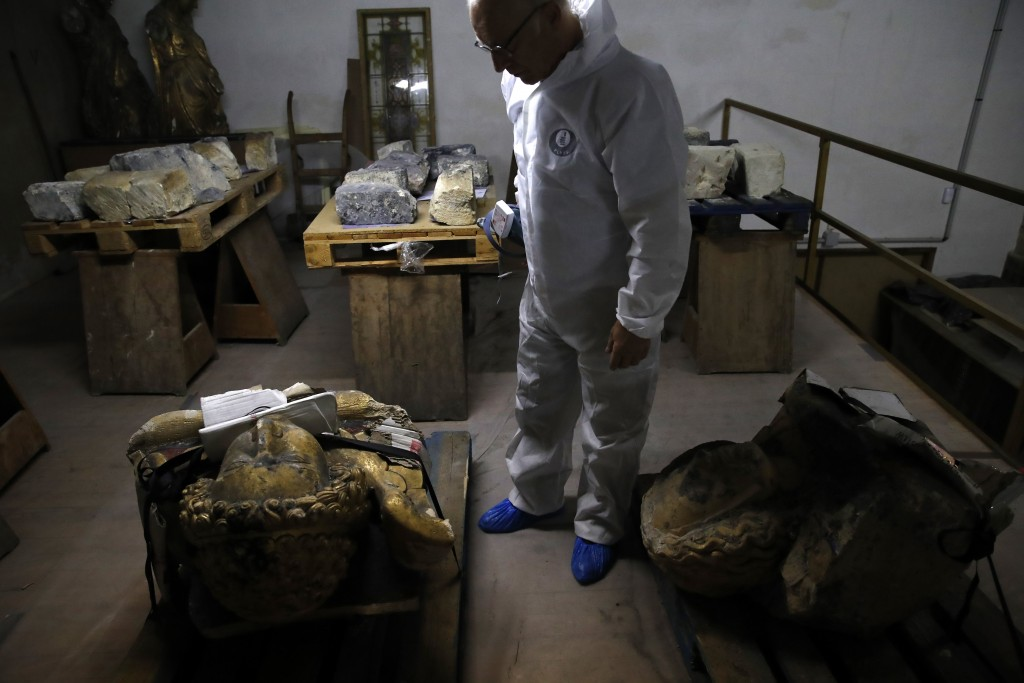 In this photo taken on Wednesday, Oct. 9, 2019, stone expert Jean-Didier Mertz, looks on next to the remains of the golden angel that was once atop No
