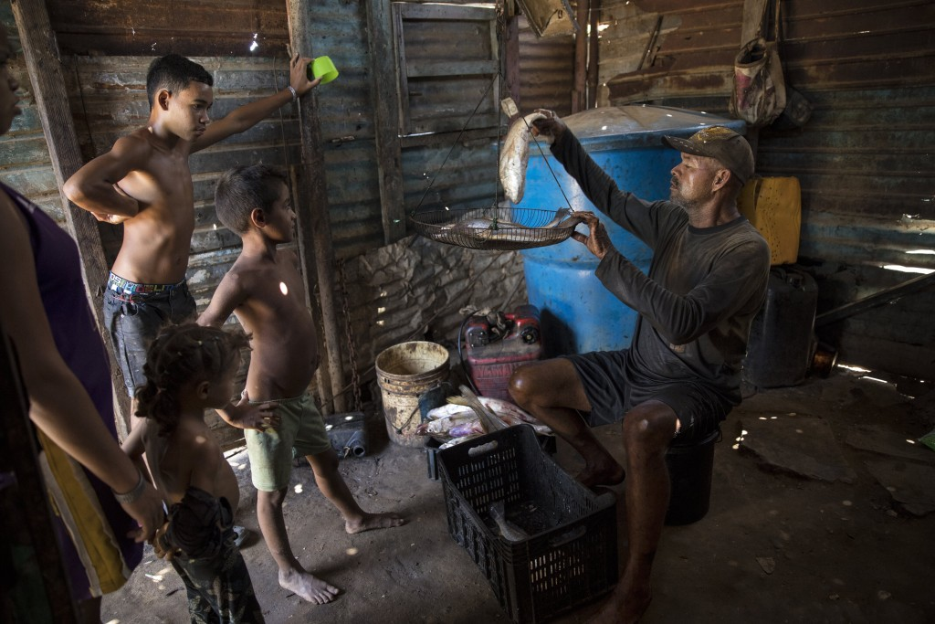 Fisherman Alejandro Elizalzabal, whose shirt is covered in oil from Lake Maracaibo, weighs his catch after a work day on the lake, in Cabimas, Venezue...