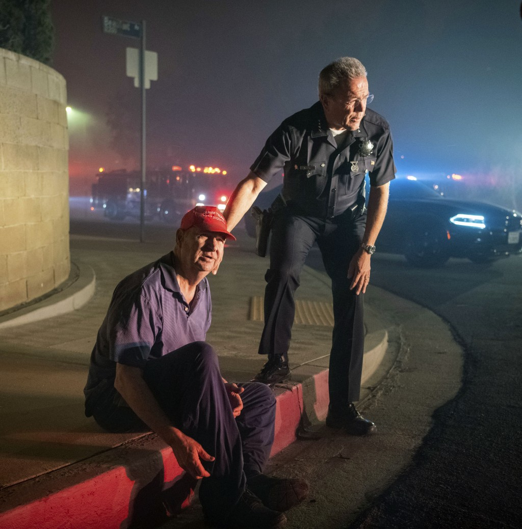 Los Angeles Police Department Chief Michel Moore tells resident Jerry Rowe that firefighters are coming after the roof of Rowe's home caught fire from...