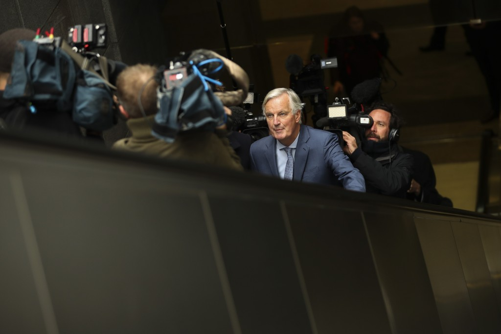European Union chief Brexit negotiator Michel Barnier, front, rides an escalator surrounded by the media on his way to a meeting at the Europa buildin...