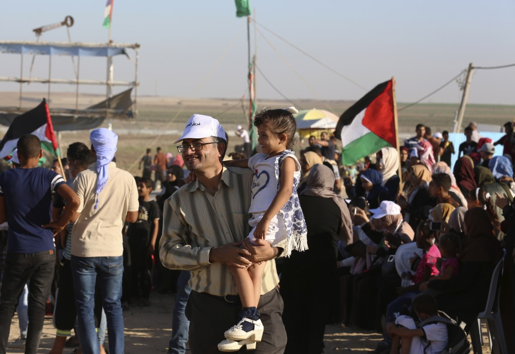 In this Sept. 25, 2019 photo, Palestinian activist Ahmed Abu Artima holds his daughter during an alternative protest he organized near the separation