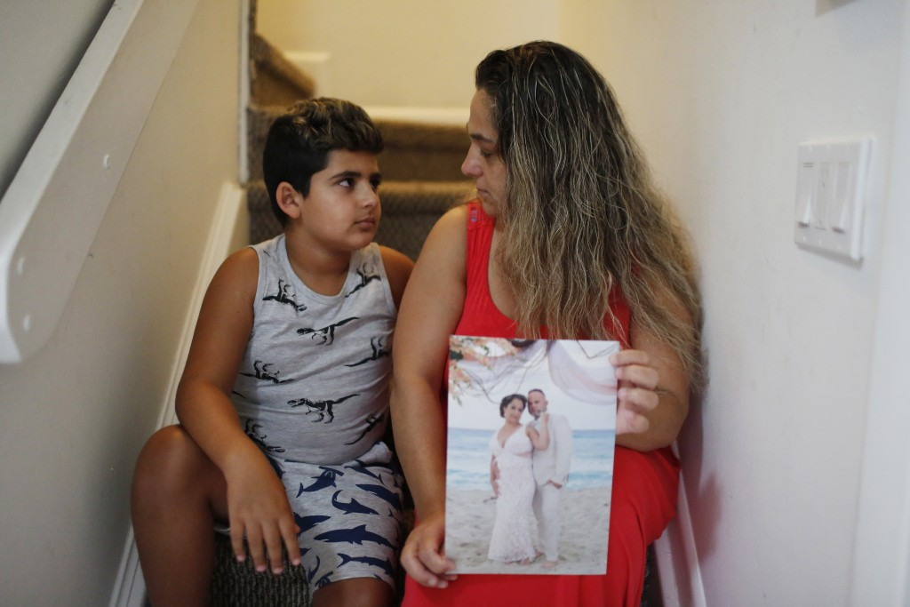 In this Aug. 6, 2019, photo, Barbara Rodriguez and her son, Nolan Aragon, 9, pose for a photograph in Hialeah, Fla. Rodriguez is holding a wedding pho