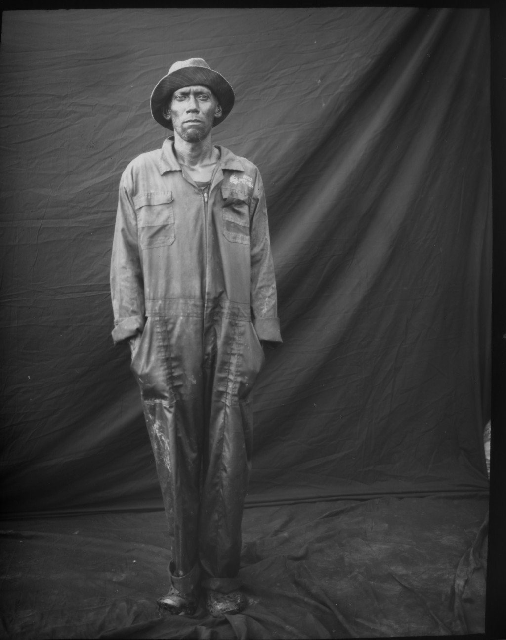 Former oil worker David Ortiz poses for a portrait in one of his old PDVSA uniforms, which he uses to work as a fisherman, after a day's work on oil-c