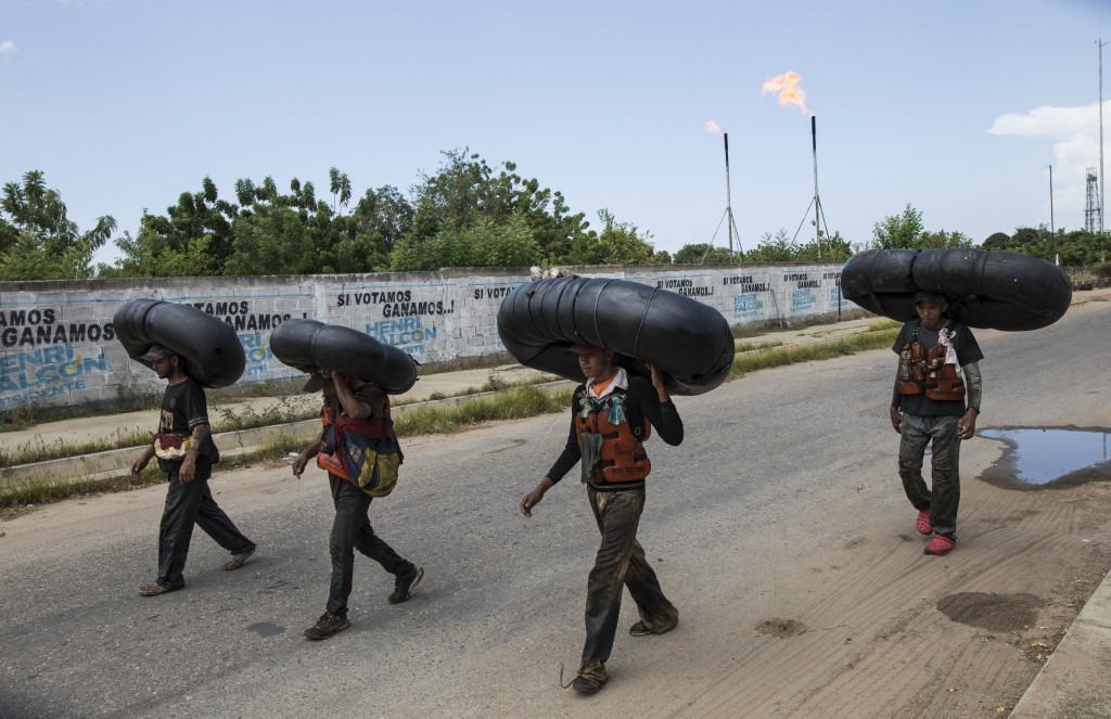 Oil-covered fishermen carry home the truck tire inner tubes they use to float on in Lake Maracaibo in Cabimas, Venezuela, July 12, 2019. Venezuelan fi...