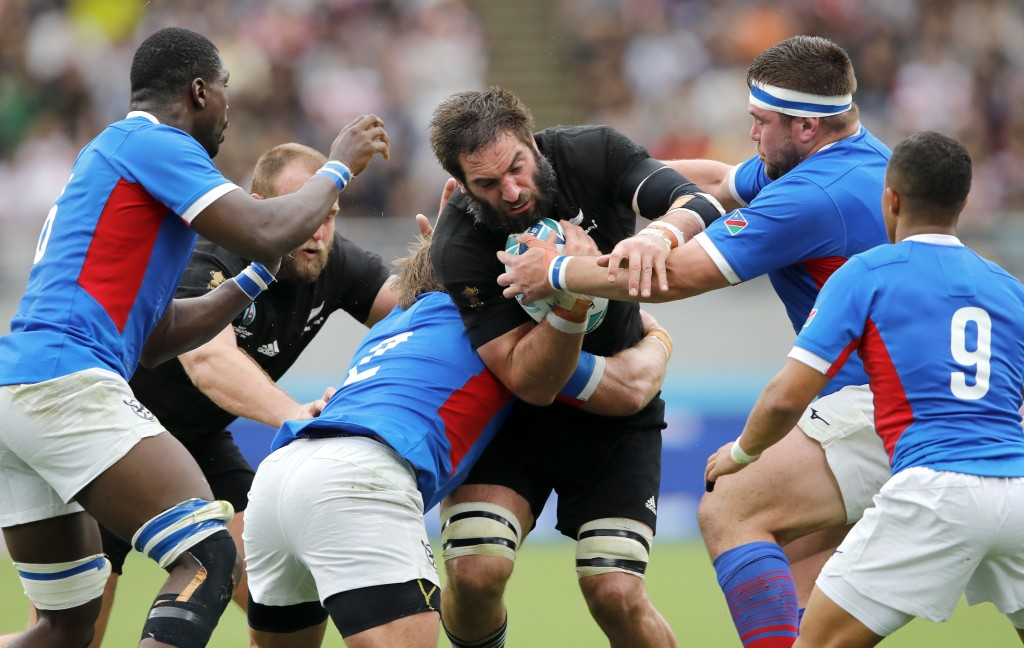 New Zealand's Samuel Whitelock, centre, runs at the Namibian defence during the Rugby World Cup Pool B game at Tokyo Stadium between New Zealand and N...