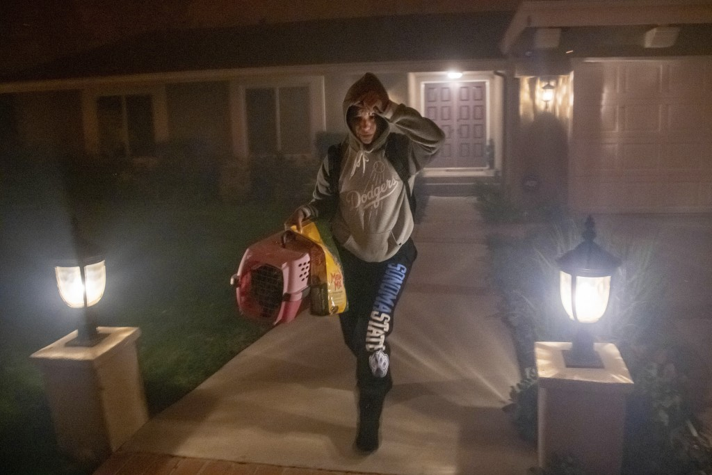 A woman evacuates her home with her cat as the Saddleridge fire threatens homes in Granada Hills, Calif., Friday, Oct. 11, 2019. (AP Photo/Michael Owe