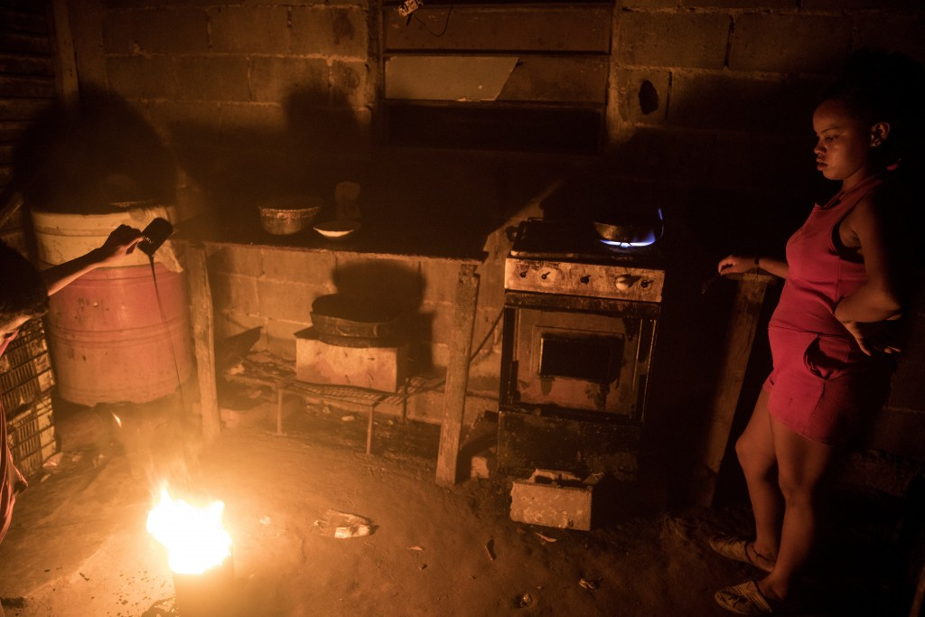 """During a blackout, oil is added to a bucket of fire, known as a """"mechurrio,"""" the name for the flares that burn excess gas on top of oil wells, inside ..."""