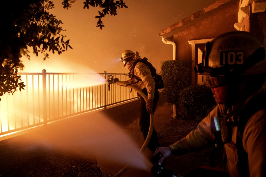 In this Thursday, Oct. 10, 2019 photo, Los Angeles City firefighters battle the Saddleridge fire near homes in Sylmar, Calif. (AP Photo/Michael Owen B