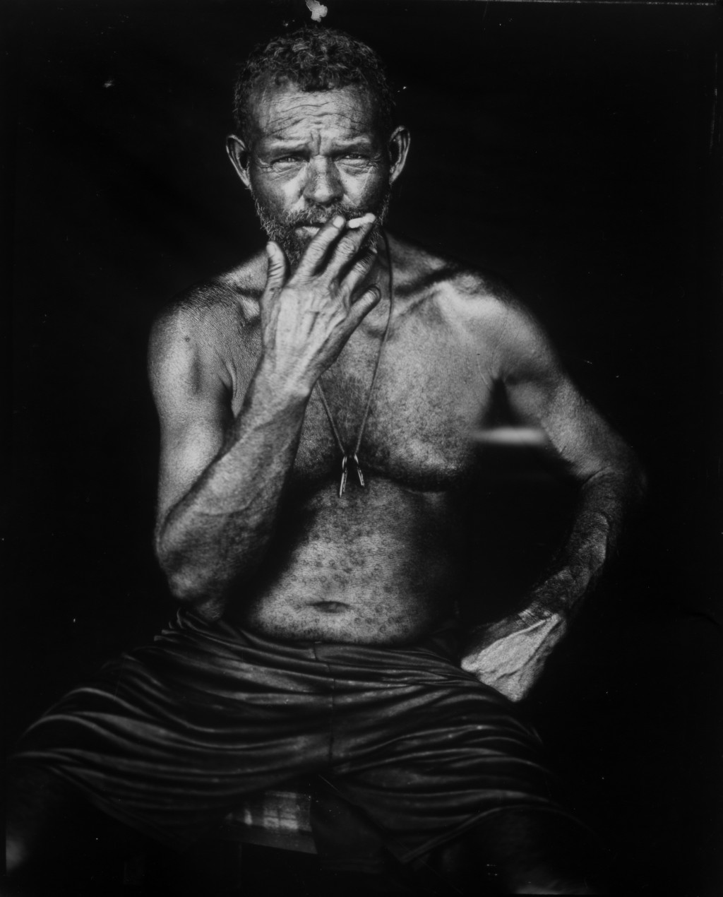 Fisherman Alejandro Elizalzabal smokes a cigarette as he sits for a portrait after a day's work on oil-contaminated Lake Maracaibo in Cabimas, Venezue