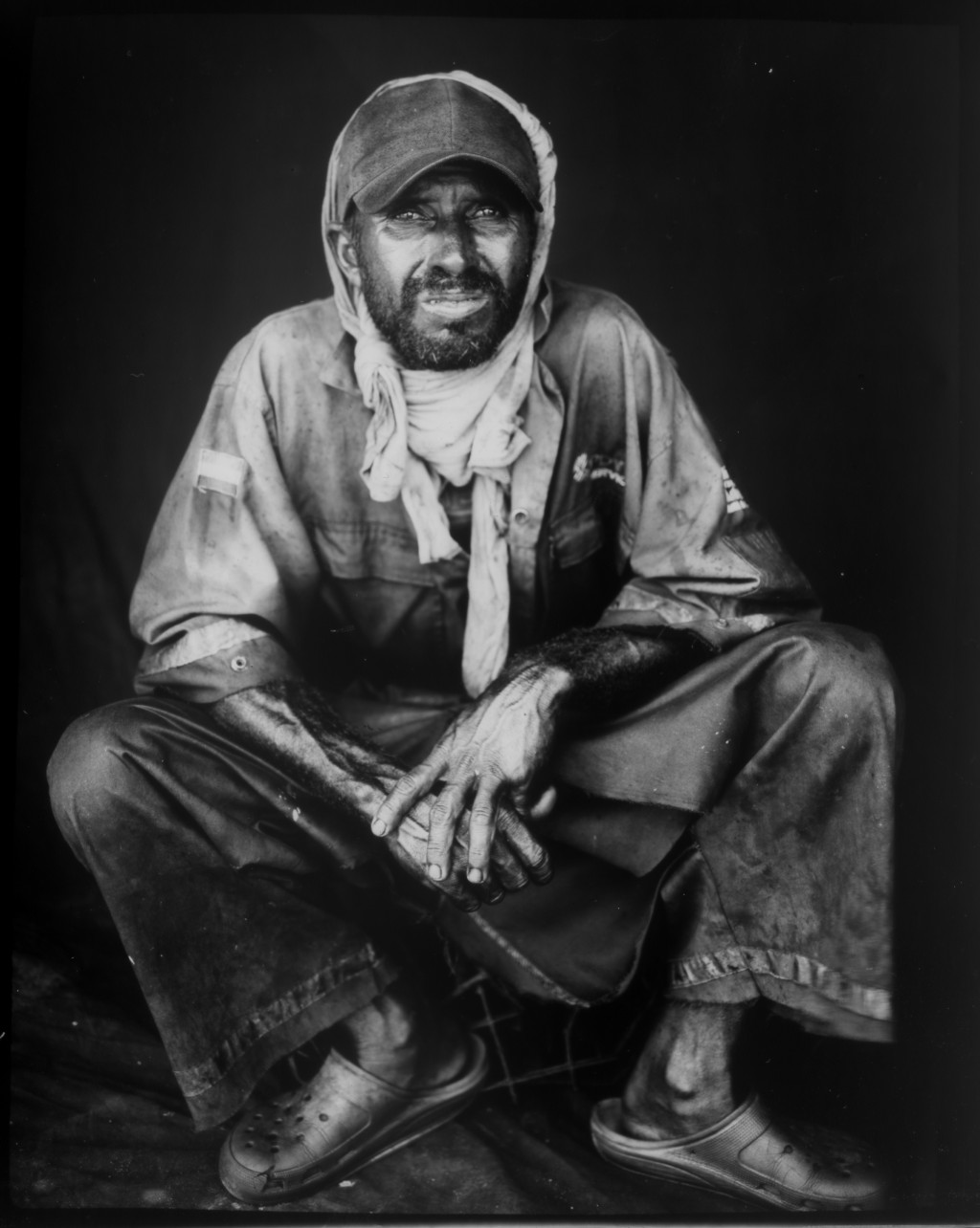 Former oil worker Jose Gregorio Romero poses for a portrait in one of his old PDVSA uniforms, which he uses to work as a fisherman, after harvesting c