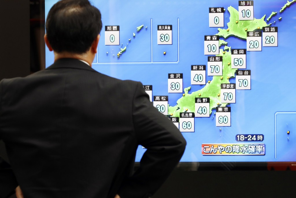 A man watches a public TV of weather forecast in Tokyo Friday, Oct. 11, 2019. Japan's weather agency is warning a powerful typhoon may bring torrentia
