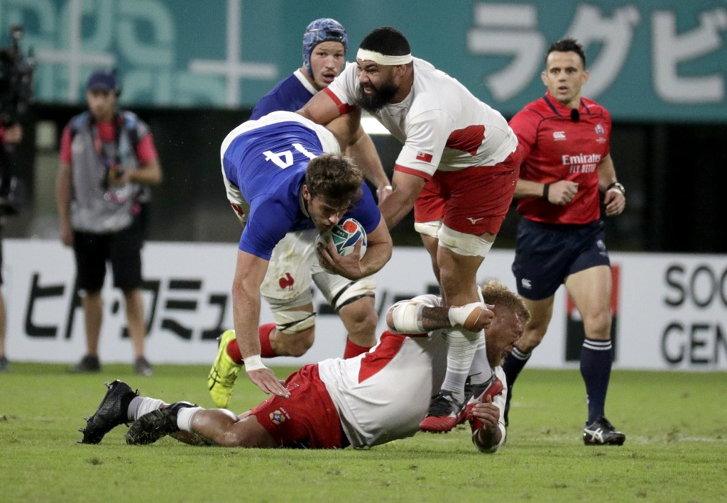 France's Damian Penaud is tackled by Tongan defenders during the Rugby World Cup Pool C game at Kumamoto Stadium between France and Tonga in Kumamoto,