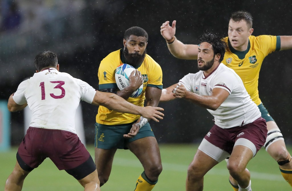 Australia's Marika Koroibete runs at Georgia's David Kacharava, left, during the Rugby World Cup Pool D game at Shizuoka Stadium Ecopa between Austral...