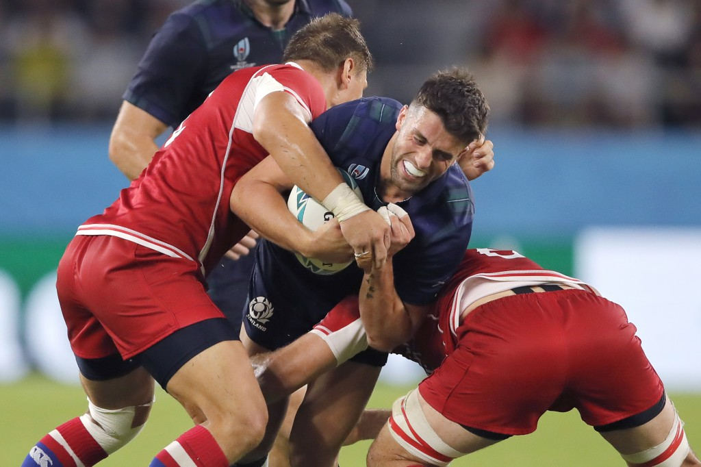 Scotland's Adam Hastings is tackled by Russia's Dmitry Gerasimov, left, and Vitaly Zhivatov during the Rugby World Cup Pool A game at Shizuoka Stadium...