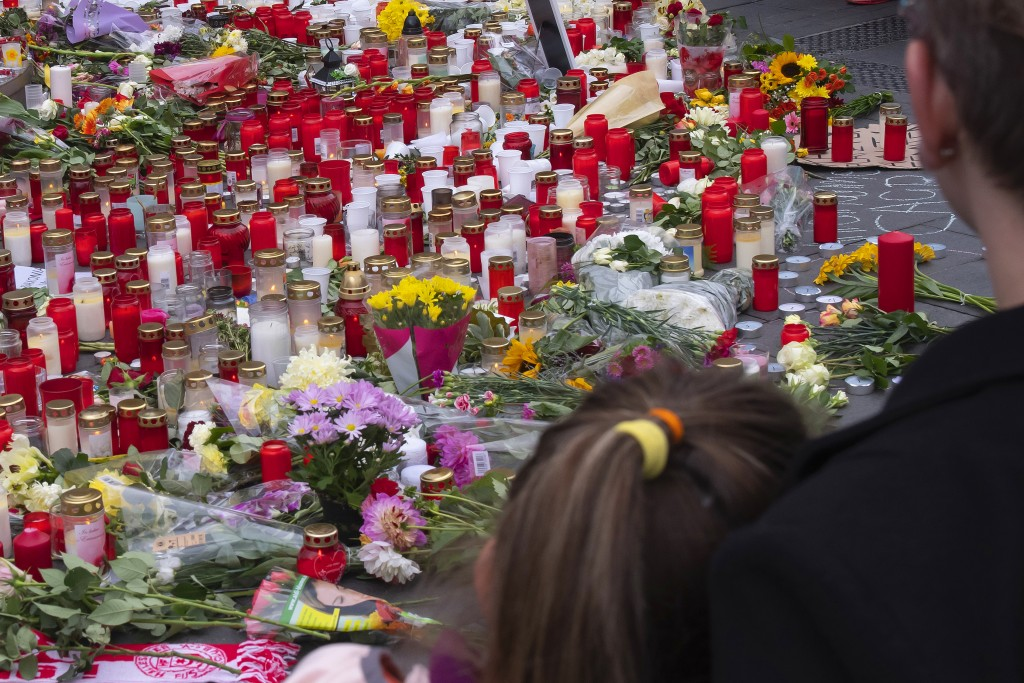 People mourn at the marketplace in the old town of Halle, Germany, Friday, Oct. 11, 2019. A heavily armed assailant ranting about Jews tried to force ...