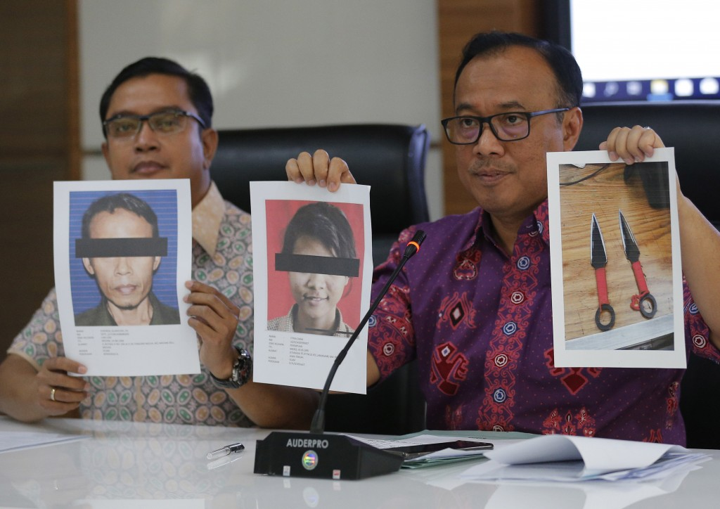 Indonesian National Police spokesperson Brig. Gen. Dedi Prasetyo, right, and an aide show photos of the suspects in the knife attack against Indonesia